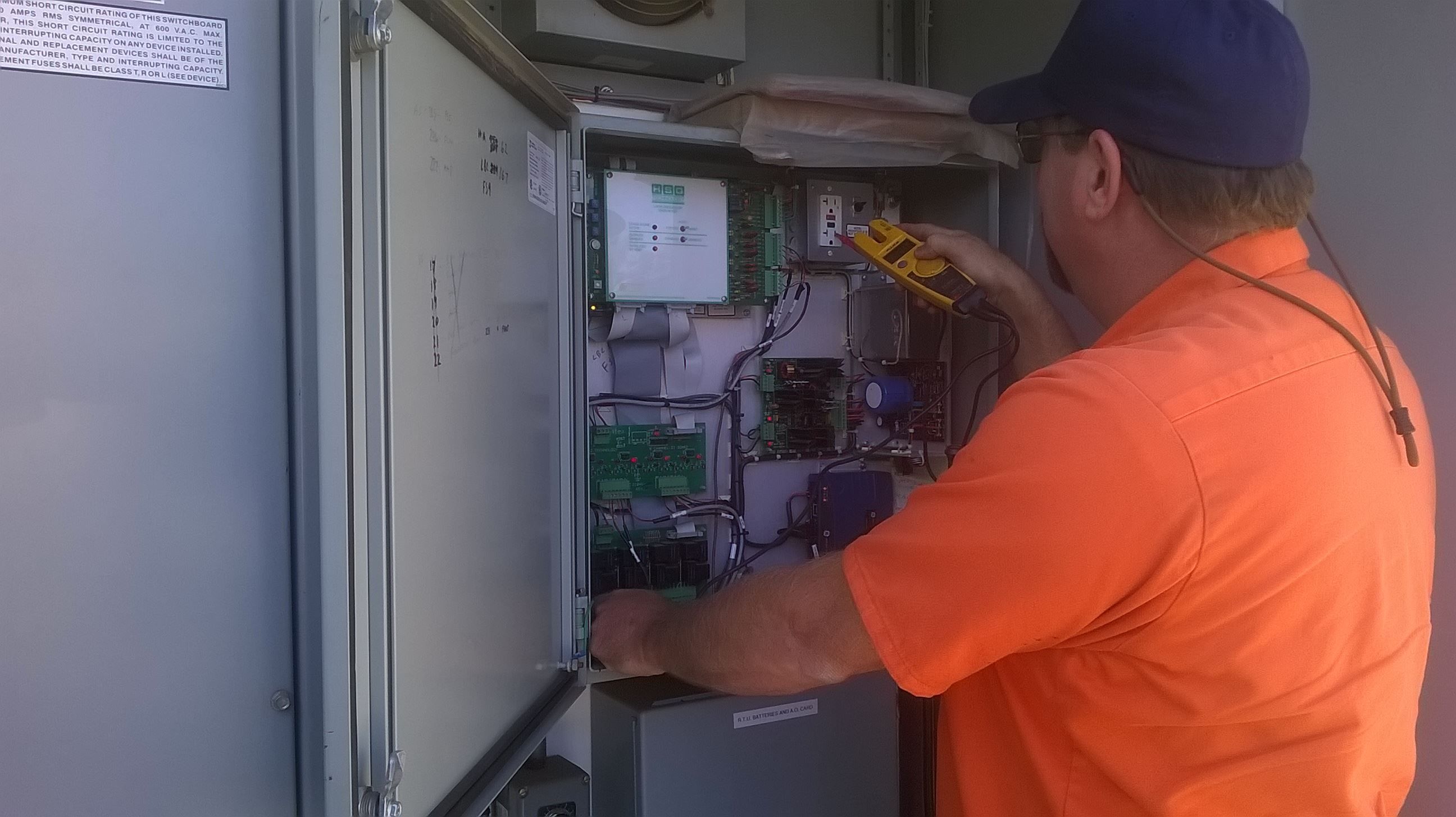 city worker tests power levels at water tank electrical box