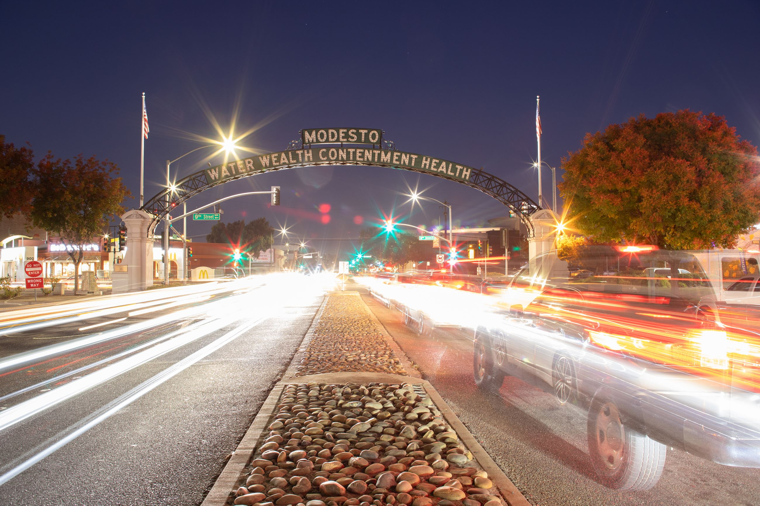 The Modesto arch is centered between two lanes of traffic in the evening.