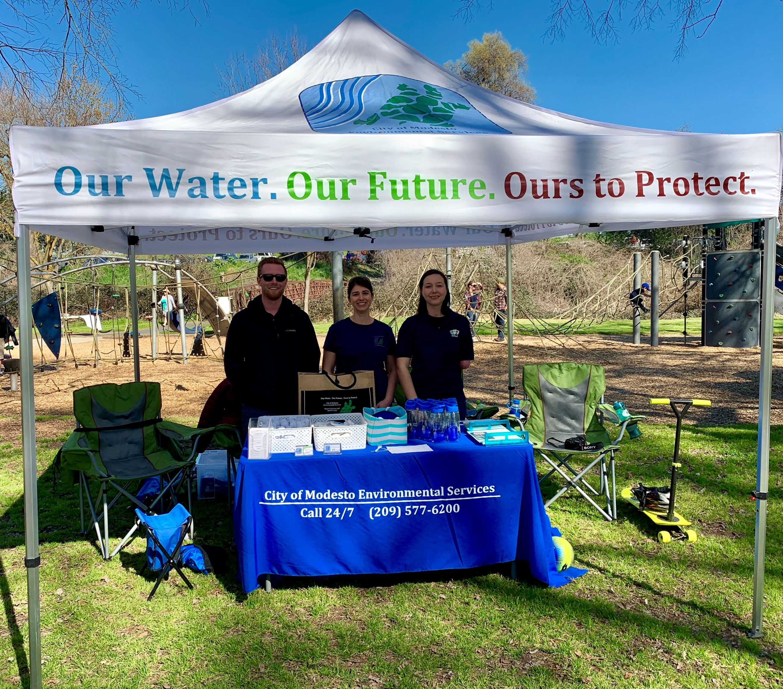 Three City employees stand at a booth display for One Water Modesto