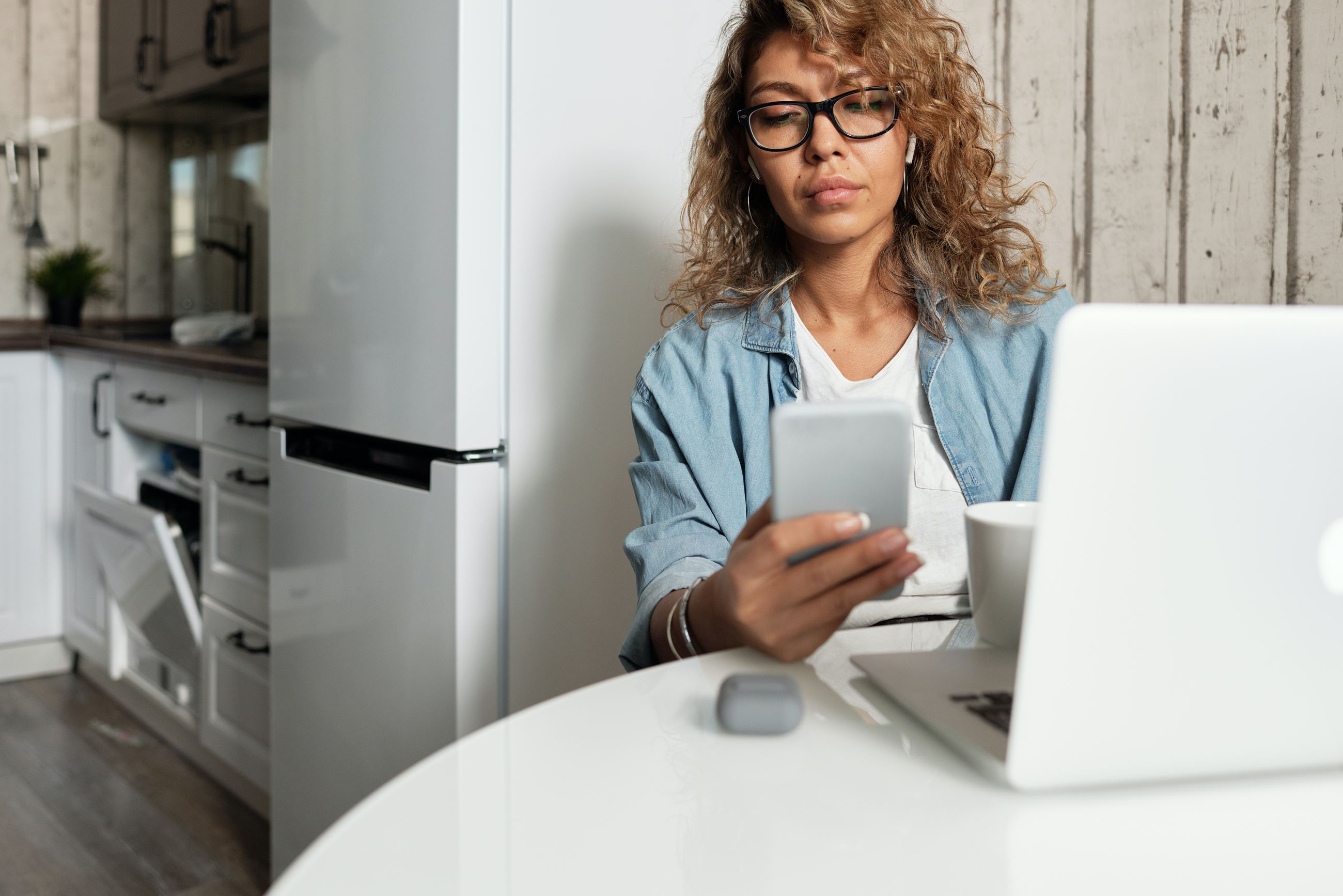 A woman looking at her phone sits at a kitchen table with her laptop open