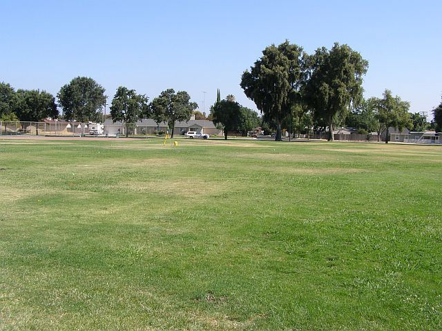 A large drying grass area with a run down baseball field in the background