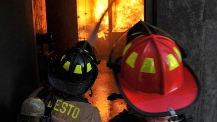 Two members of the Modesto Fire Department work to enter and extinguish a building on fire.