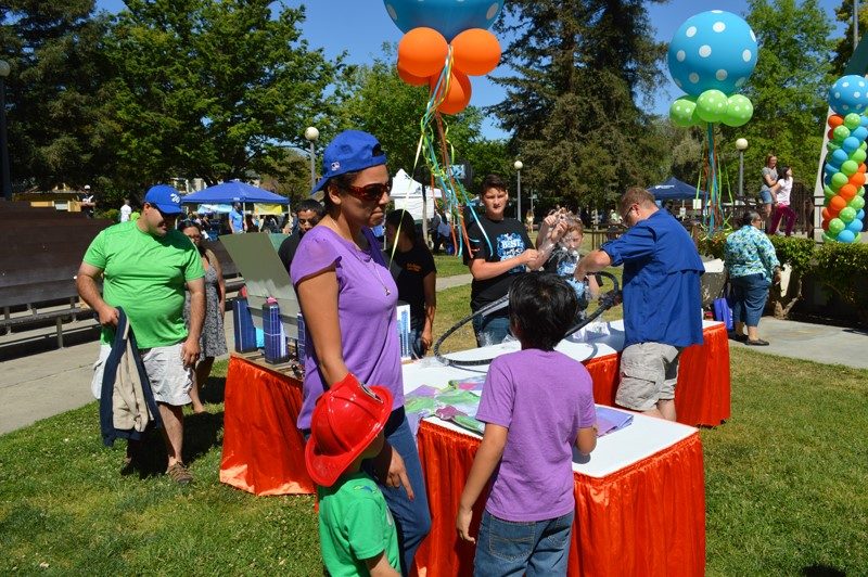 Children and Adults Learning at an Earth Day Booth